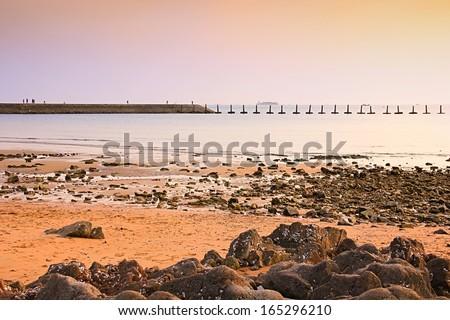 Long bank on seashore at sunset. - stock photo