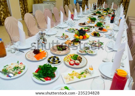 Long banquet table. On the table, drinks and snacks. A table covered with a white tablecloth. Around there are chairs in the covers. - stock photo