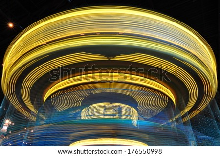 long blurred exposure of ride at carnival - stock photo
