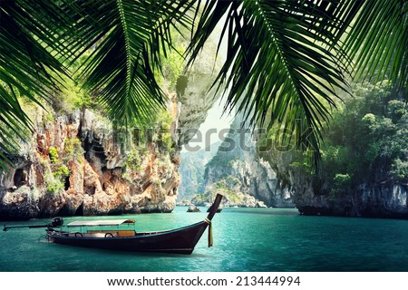long boat and rocks on beach in Krabi, Thailand - stock photo