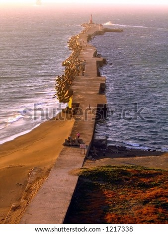 Long Breakwater with Concrete Blocks -- illuminated by the afternoon sun - stock photo