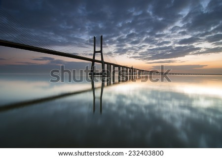 Long bridge over tagus river in Lisbon at dawn - stock photo
