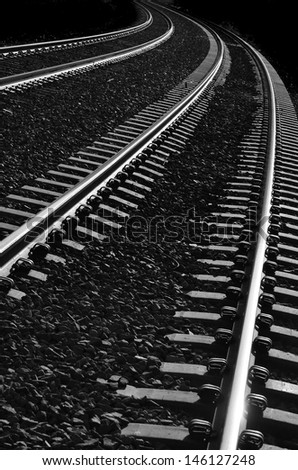 Long bright, railroad tracks curving around bend - stock photo