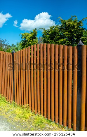 Long brown wooden fence protecting private property - stock photo