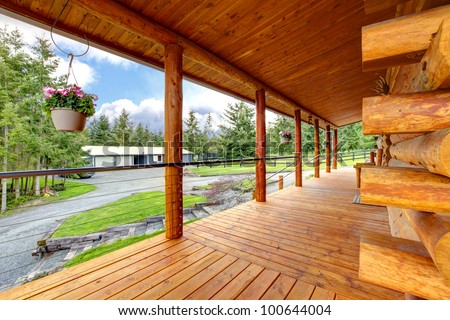 Long cabin horse farm house porch with view on the horse shed. - stock photo