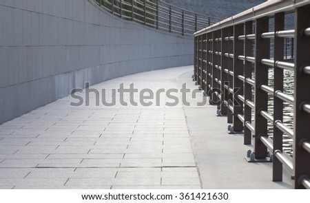 Long concrete pathway and metal fence beside a building - stock photo