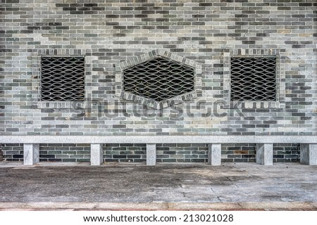 Long concrete seat and grey brick wall - stock photo