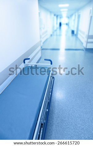 Long corridor in hospital with surgical gurney. Tinted picture - stock photo
