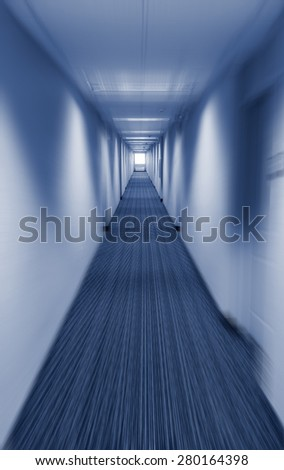 Long corridor vanishing point with applied motion blur filter in cold blue tint a creepy place or tunnel vision concept - stock photo