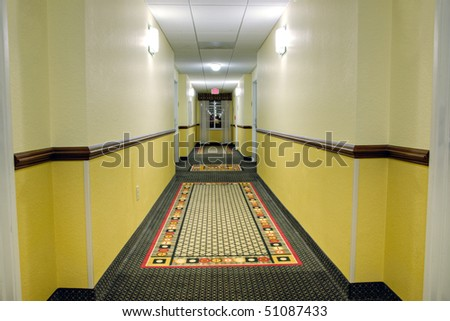 Long corridor with a window in modern hotel showing patterned carpet - stock photo