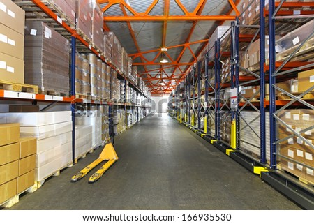 Long corridor with shelving system in distribution warehouse - stock photo