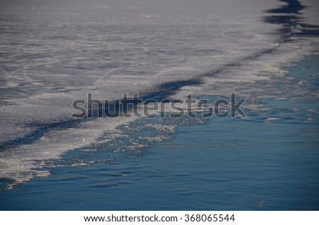 long crack in the ice on the lake in the winter - stock photo