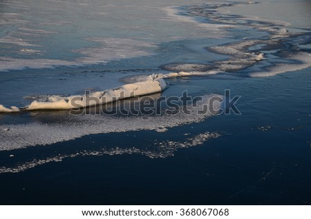 long crack in the ice with snow on the lake - stock photo