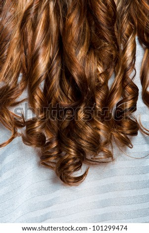 long curly professionally dyed red hair on silver background. - stock photo