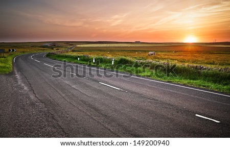 Long curved road during a sunset/sunrise in north Scotland - stock photo