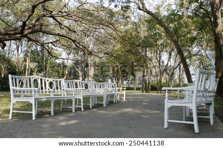 Long curved row of white park benches  - stock photo