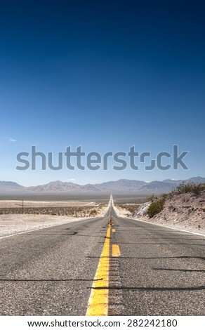 Long Distant Highway Under the Sun Across Death Valley National Park. Vertical Image Composition - stock photo
