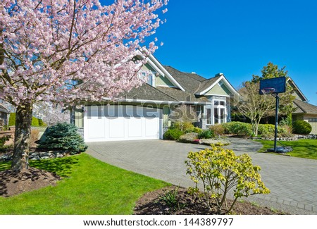 Long driveway to the double garage doors and nicely trimmed and landscaped front yard at cherry blossom time in the suburbs of Vancouver, Canada.