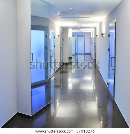 Long, empty corridor in a hospital or office building, with the ceiling lights reflected on the shiny floor. - stock photo