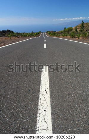 Long empty road in vulcanery landscape. - stock photo