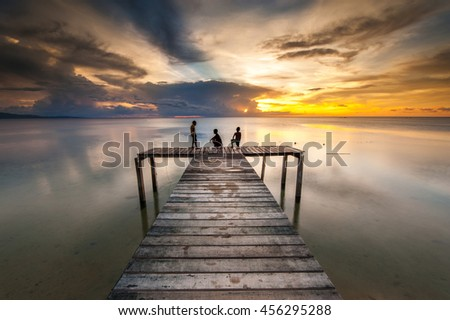 long expose sunset at Kudat Sabah. three unknown kids appear on the image. image contain soft focus and blur.