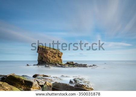 Long Exposure at Collywell Bay / A rocky outcrop and Sea Stack known locally as Charlie's Garden in Collywell Bay, Seaton Sluice on the Northumberland coast - stock photo