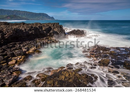 Long exposure at Queen's bath on the island of Kauai, Hawaii. Large waves crashing on the lava rocks and into the tide pools. - stock photo