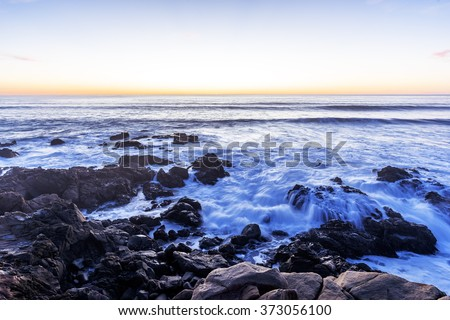 Long exposure at sunset (golden hour) on a rocky shoreline, with waves breaking over the rocks, traveling the Big Sur Highway, on the California Central Coast, near Cambria CA.