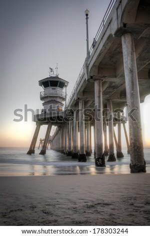 Long exposure captures slow moving waves under The Huntington Beah Pier in Huntington Beach, California - stock photo