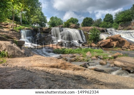 Long exposure captures the slow flowing Reedy River at Falls Park - stock photo