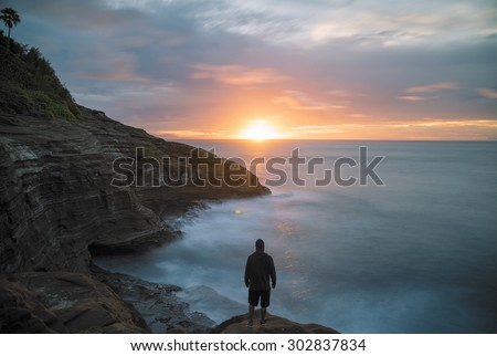 Long exposure creating a motion blur of sunrise from the cliffs on the east coast of Oahu, Hawaii overlooking the ocean. A man standing in the foreground looking down the coast toward the sun.  - stock photo
