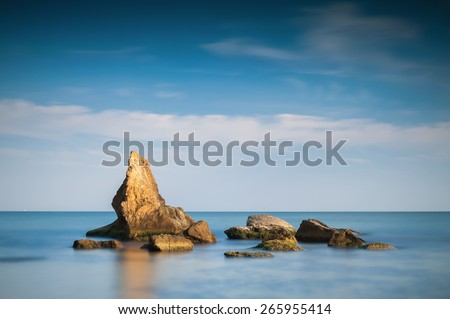 Long exposure day photo of rocks in the calm sea with some clouds in the back - stock photo