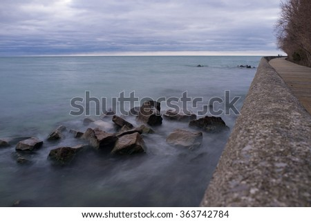 long exposure ice top rock in the lake - stock photo
