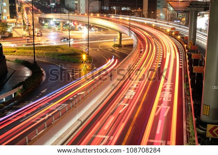 Long exposure image of cars rushing over a highway in central Tokyo, Japan at night - stock photo