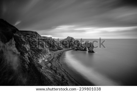 Long exposure image of Durdle Door rock arch seen from the cliff top.