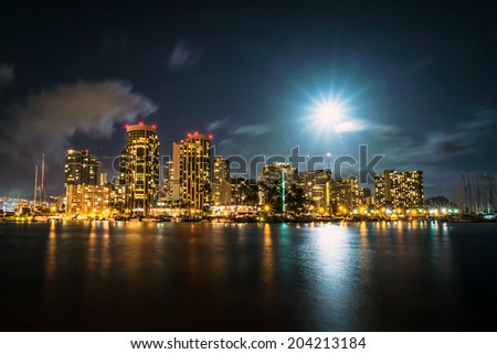 Long exposure image of full moon over Ala Wai Boat Harbor and Waikiki with Diamond Head in distant background.  - stock photo