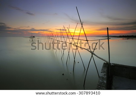 "Long exposure image of ""langgai"" during beautiful sunset , the traditional fishing medium at Malaysia . Images has grain texture - noise seen at 100 percent of its size."