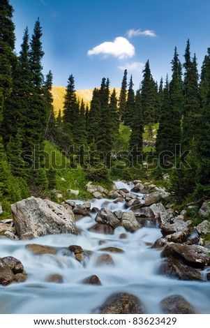 Long exposure image of mountain river falling and flowing trough stone at nature - stock photo