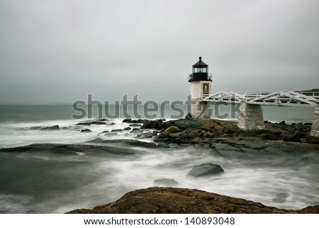 Long exposure image of the Marshall Point Lighthouse in heave seas high surf and rain - stock photo
