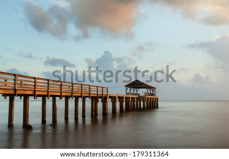 Long exposure image of Waimea pier at sunset blurs the ocean and bathes the structure in the warm glow of the setting sun. Taken on island of Kauai in Hawaiian islands - stock photo