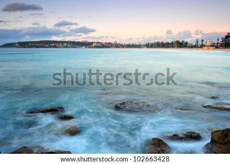 long exposure make aqua blue green sea ocean waves mystical as sun rises over manly beach, sydney, australia - stock photo