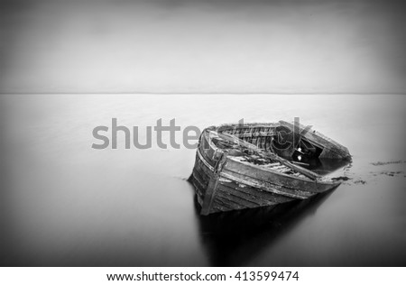 Long exposure of a abandoned boat in black and white - stock photo
