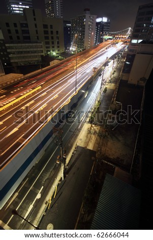 Long-exposure of a busy city highway through urban Tokyo, Japan at night - stock photo