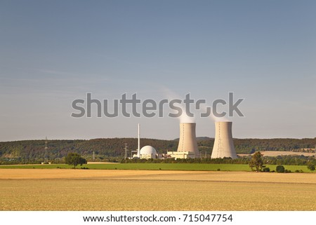 Long exposure of a nuclear power station with hill landscape and blue sky.