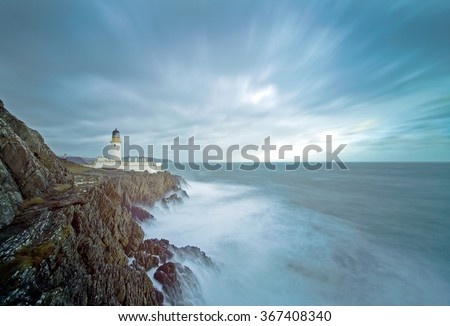 Long Exposure of a Stormy Sea with Lighthouse on top of Rocky Cliffs. Location, Douglas, Isle of Man, United Kingdom - stock photo