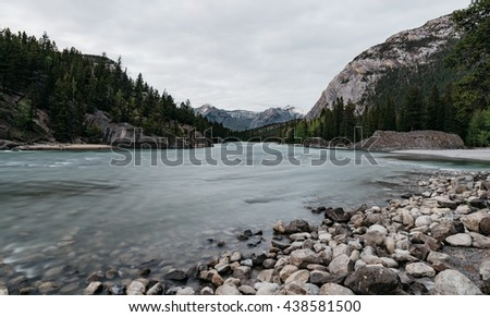 Long Exposure of Bow River against rocks during sunset with Canadian Rockies in the background, Banff National Park, Alberta, Canada - stock photo