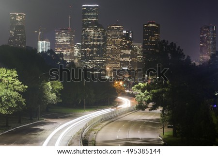 Long-exposure of cars racing over a freeway in downtown Houston, Texas with the Houston skyline in the background at night