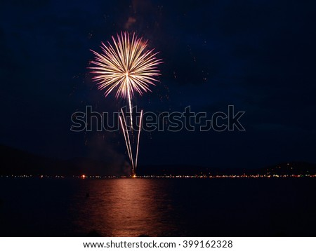 Long Exposure of Fireworks Reflecting on Calm Rippling Lake Water - stock photo