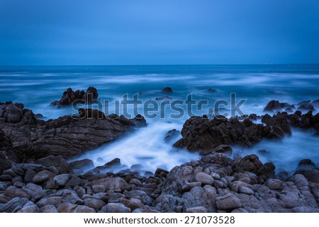 Long exposure of rocks and waves in the Pacific Ocean at twilight, in Pacific Grove, California.