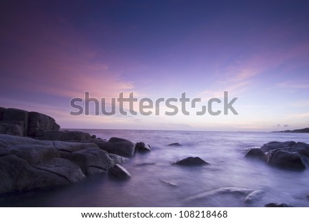 Long exposure of rocky shore over sunset in Thailand - stock photo